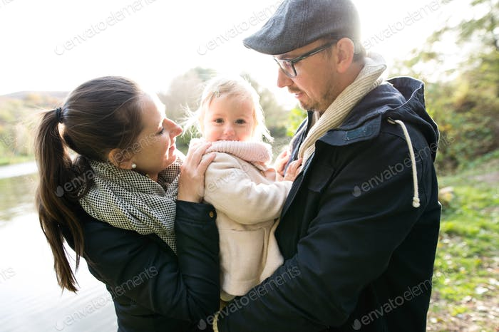 Beautiful younf family with little girl in autumn nature