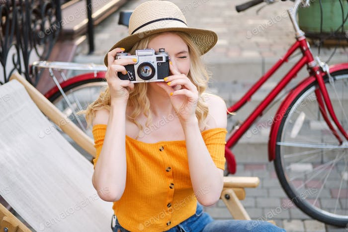 Attractive blond girl in hat dreamily taking photo on film camera sitting in street cafe