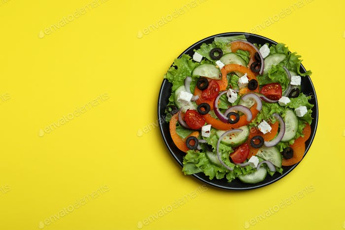 Plate of greek salad on yellow background