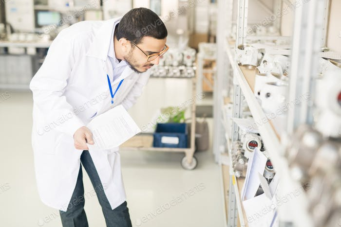 Busy Arabian engineer examining devices in warehouse