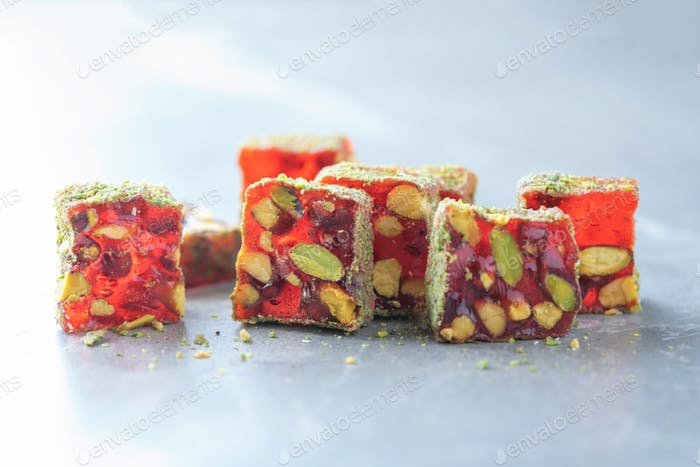 Turkish delight - lokum or rahat lokum with pistachios on grey background. Traditional eastern