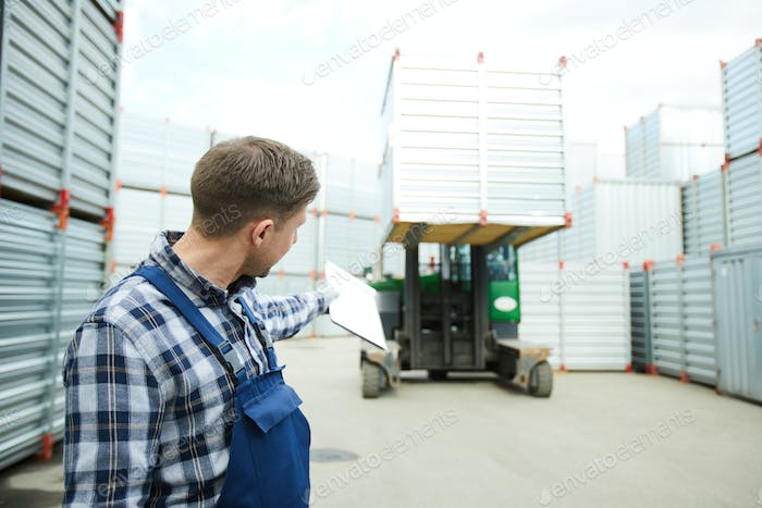 Worker showing direction to forklift driver