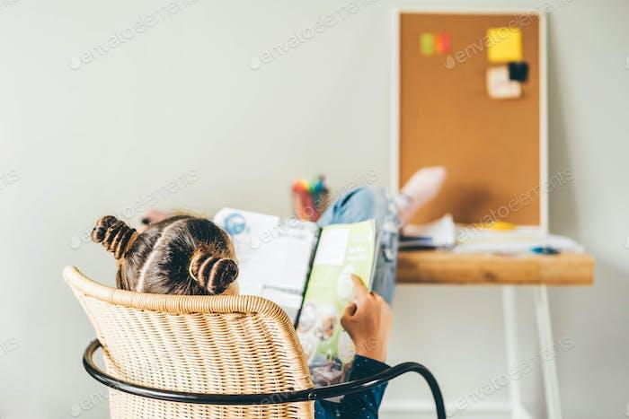 Schulmädchen lesen Buch am Schreibtisch.