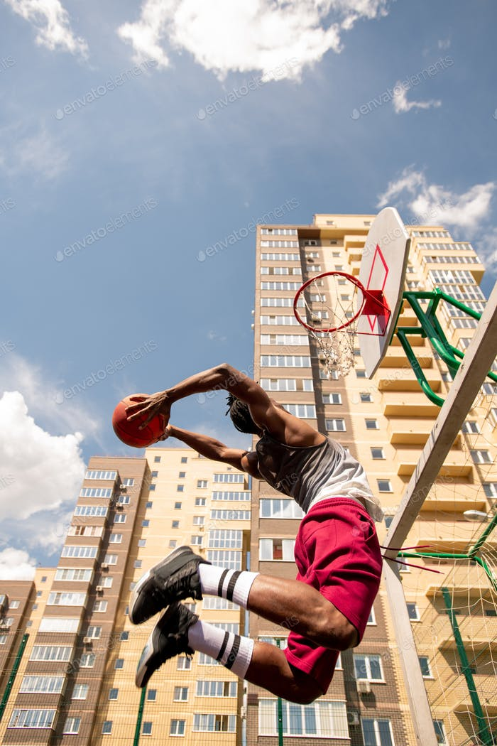 View from below of young African basketballer in jump throwing ball in basket