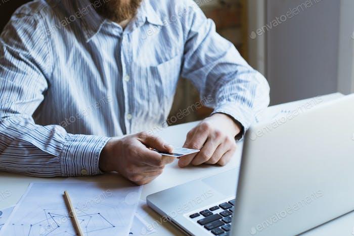 Mann, der auf Laptop-Computer arbeitet