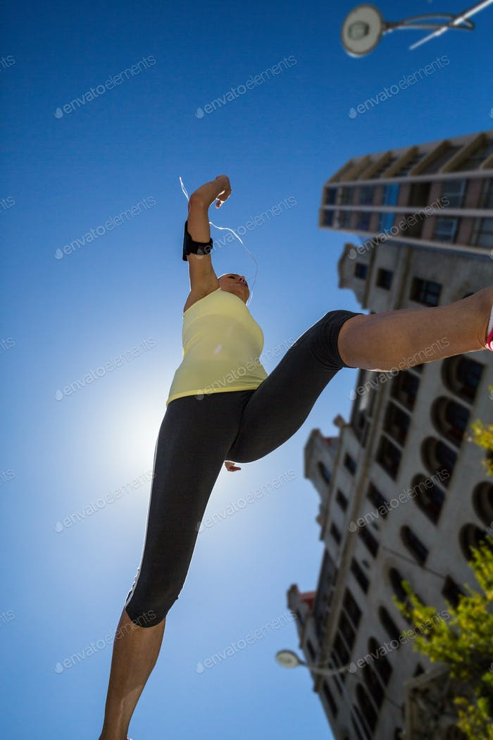 A beautiful woman jumping in the street on a sunny day