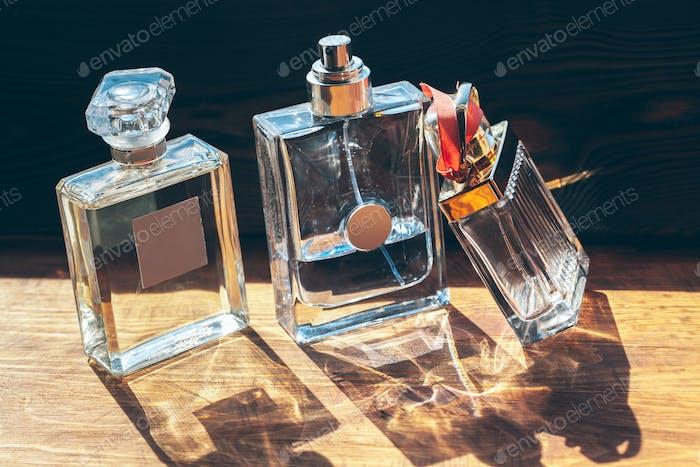 Mehrere Flaschen mit Parfüm in Sonnenstrahlen auf Holztisch