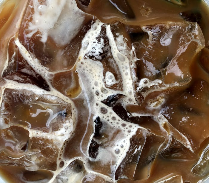 Closeup of iced coffee with milk and caramel , top view