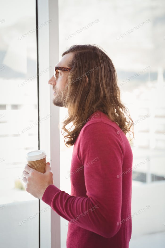 Side view of man holding disposable cup while looking through window in office