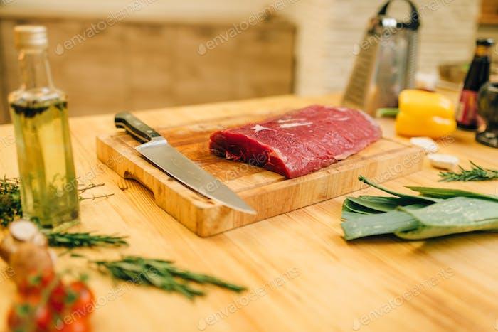 Raw meat tenderloin on board closeup, nobody