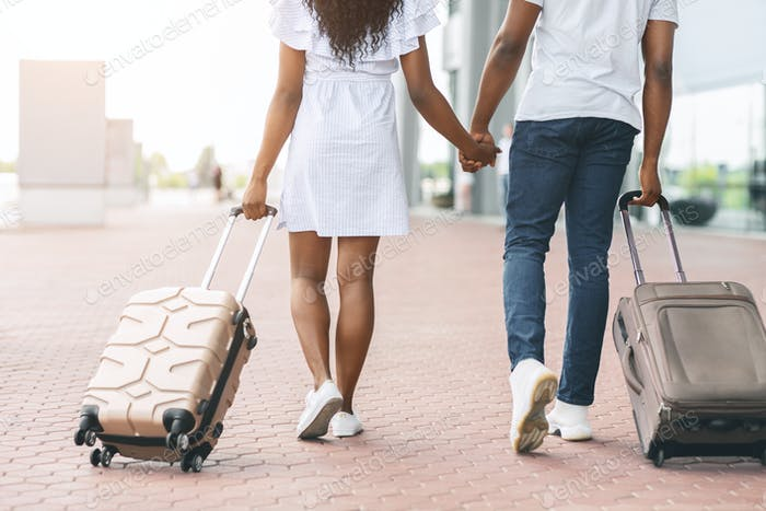Millennial african travellers going with luggage at airport
