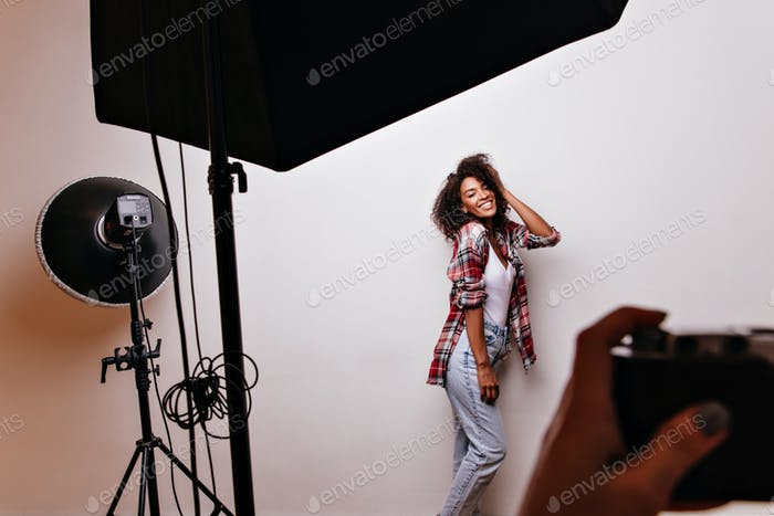 Happy female model with cheerful smile looking at photographer. Indoot shot of amazing african woma