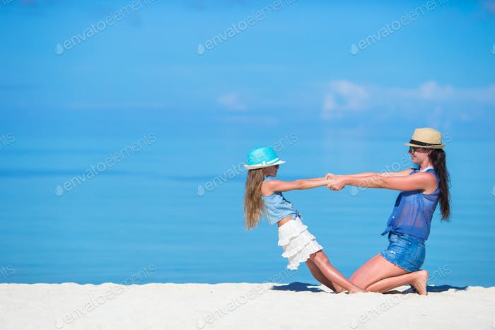 Little girl and young mother during beach vacation