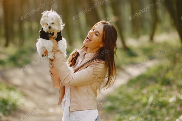 Brunette in a forest walks with cute dog