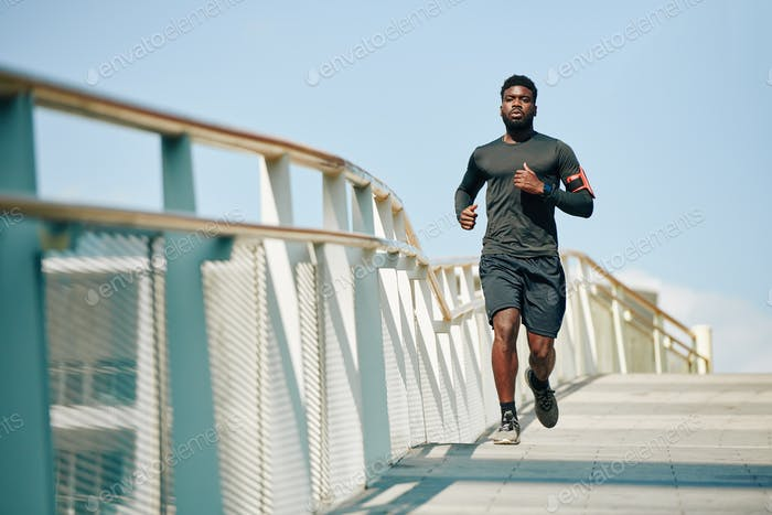 Sportsman jogging on bridge