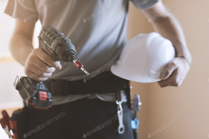 Construction worker posing with safety helmet and drill