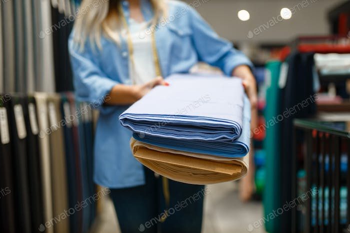 Seller holds stack of fabric in textile store