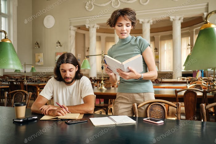 Tutor girl with book explaining to young student new topic during lesson in university library