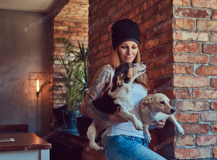 A stylish tattoed blonde female in t-shirt and jeans holds two cute dogs.
