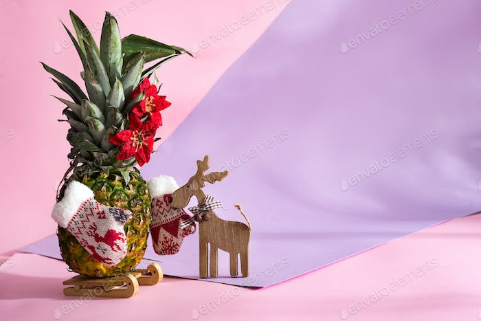 pineapple christmas tree with winter mittens and Christmas flowers on green leaves
