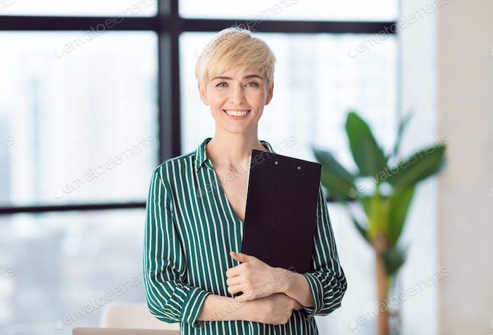 Entrepreneur Lady Holding Folder Smiling Standing Near Window In Office