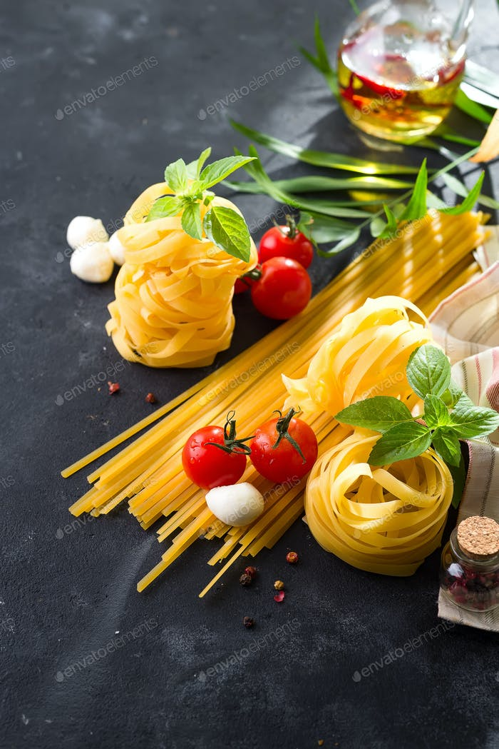 Pasta background. Several types of dry pasta with vegetables and herbs on a dark stone table.