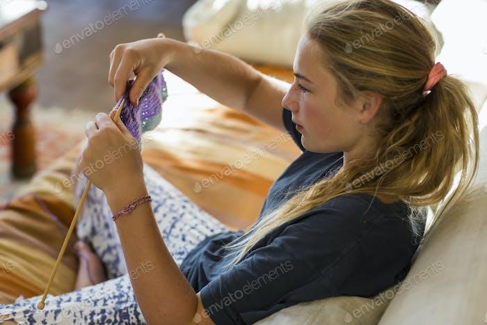 13 Jahre altes Mädchen stricken auf der Couch im frühen Morgenlicht