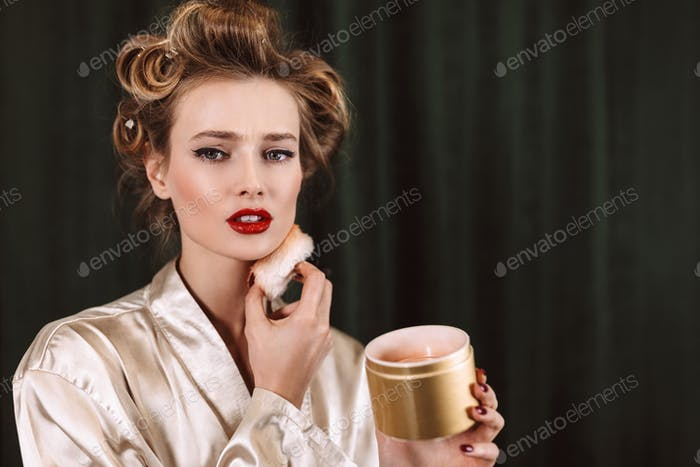 Young beautiful serious woman with wavy hairstyle and red lips i