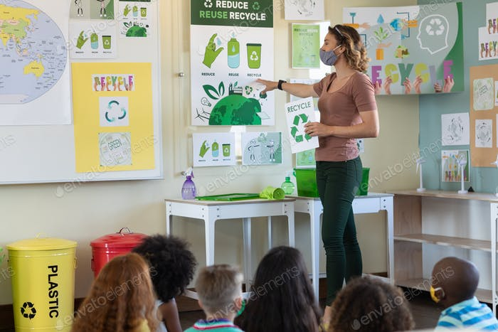 Female teacher wearing face mask showing recycling posters to students in class