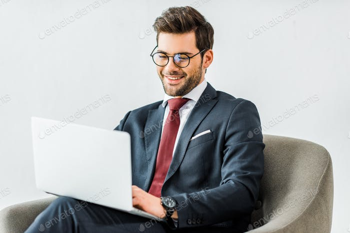 smiling businessman in formal wear sitting on armchair and using laptop in office