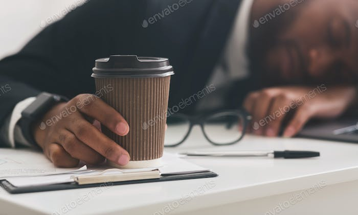 Cup of coffee in sleeping young businessman hand