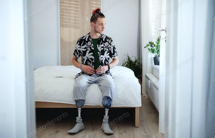 Porträt eines behinderten jungen Mannes, der zu Hause drinnen im Bett sitzt, Beinprothetikkonzept