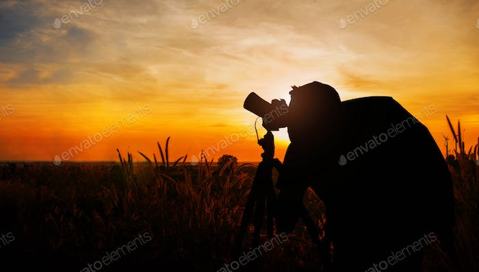 Photographers in meadow with silhouette
