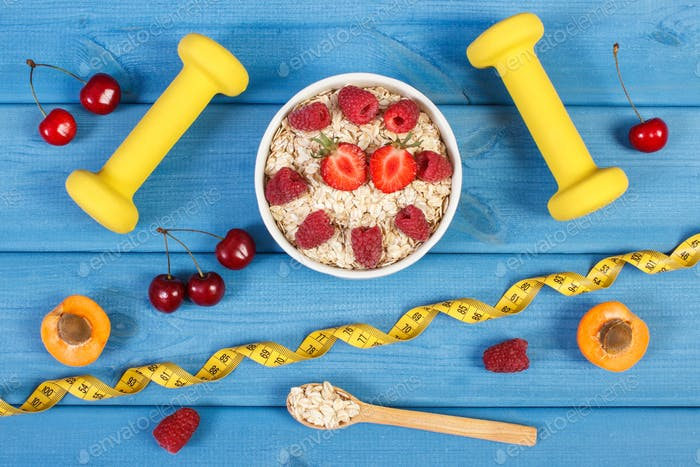 Oat flakes with fruits, dumbbells and centimeter, concept of slimming and healthy lifestyle