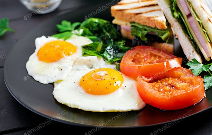 Breakfast: fried egg, spinach, tomatoes and club sandwich on plate.