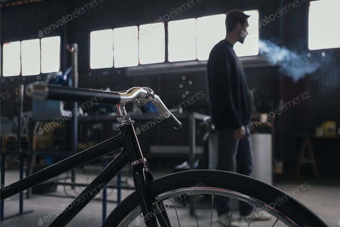 Unrecognizable man smoking with bicycle on foreground