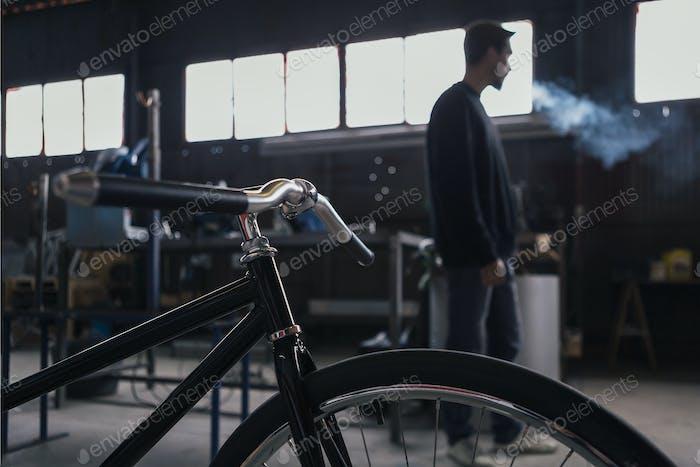 Unerkennbarer Mann Rauchen mit Fahrrad im Vordergrund