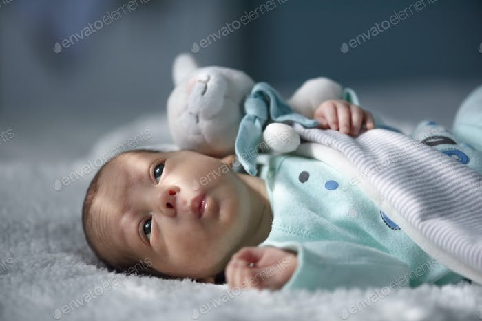Newborn baby boy on white carpet closeup