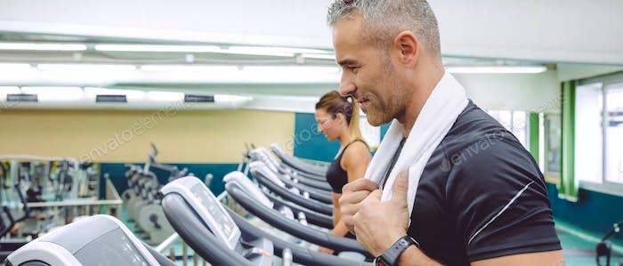 Portrait of man training over treadmill