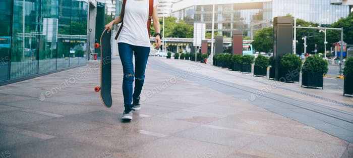 Woman walking with skateboard in hand at city