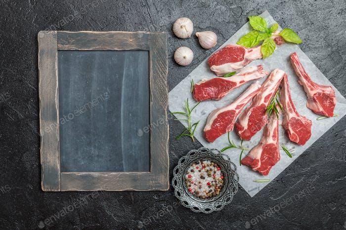 Raw lamb chops with salt, pepper, rosemary