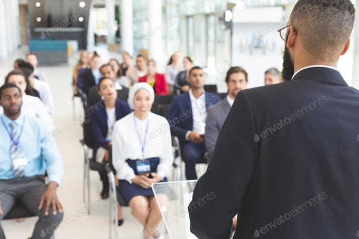 Male speaker speaks to diverse business people  in a business seminar in a conference room