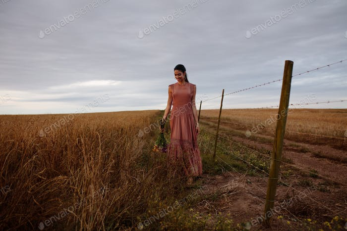 Woman walking in a field with flowers