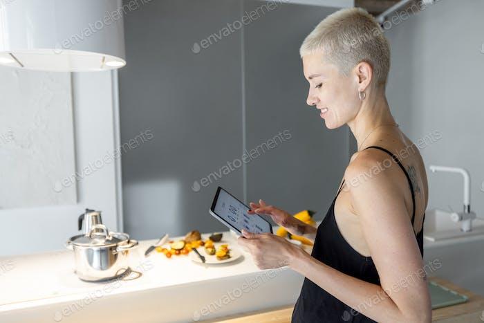 Woman controls smart kitchen appliances with mobile device