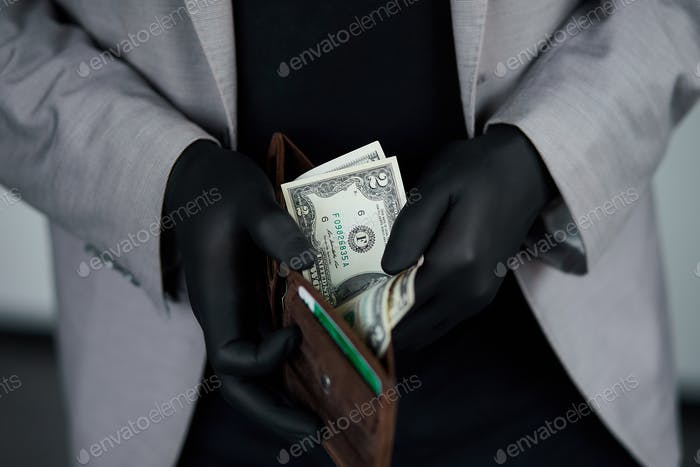 Man holding a wallet with  money dollars  in hand in black medical gloves.
