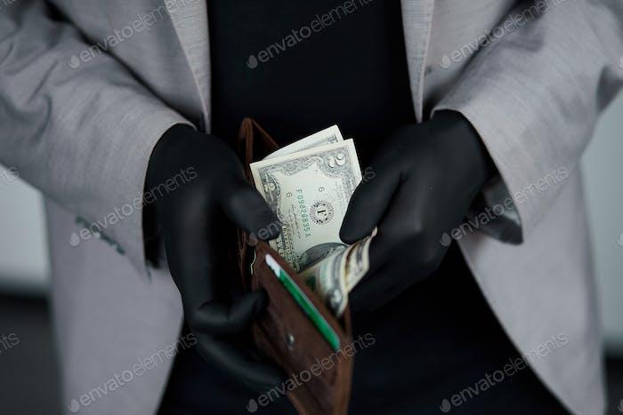 Mann hält eine Brieftasche mit Geld Dollar in der Hand in schwarzen medizinischen Handschuhen.