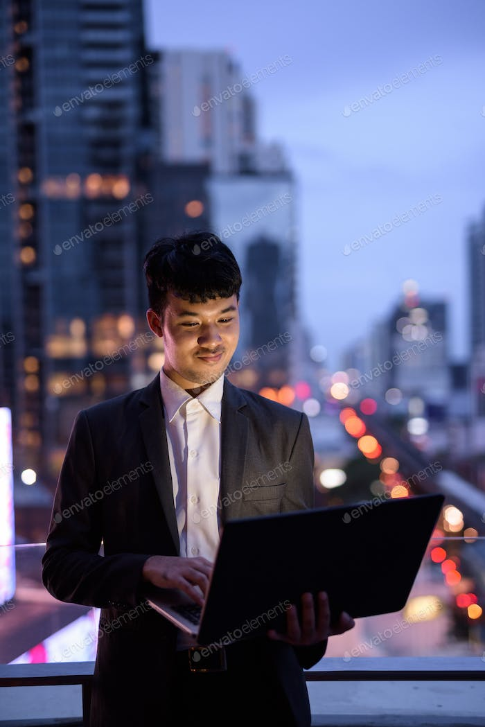 Portrait of young Asian businessman using laptop against view of the city