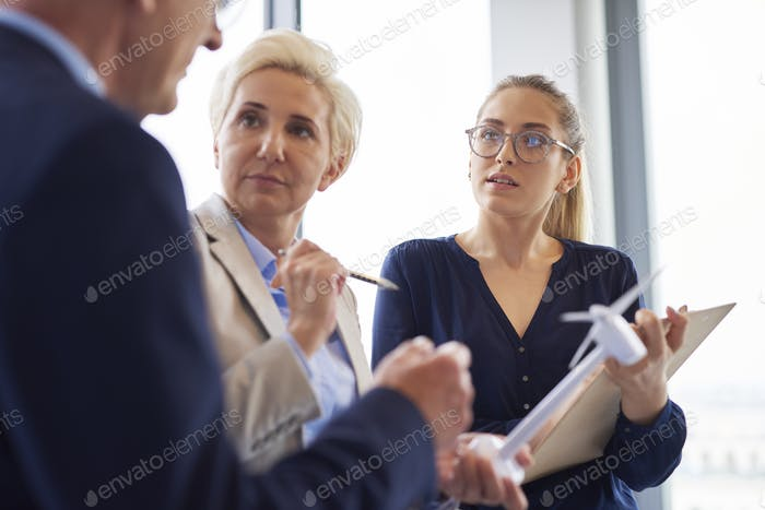 Besetzte Büroangestellte, die ein Gespräch im Büro haben