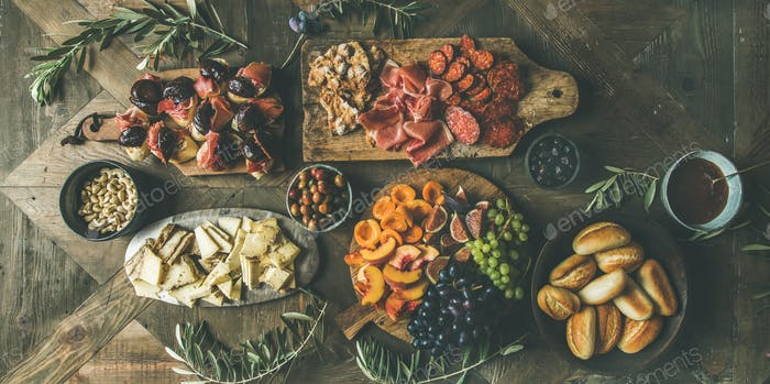 Meat, cheese, olives, sandwiches, prosciutto, buns on wooden background