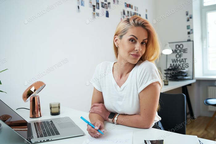 Caucasian secretary looks at camera with joyful face in modern office